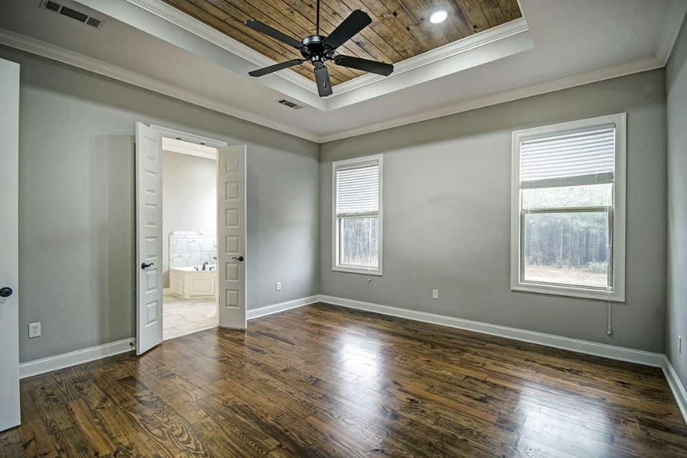 Primary bedroom with hardwood flooring, tray ceiling, and a white double door leading to the primary bath.