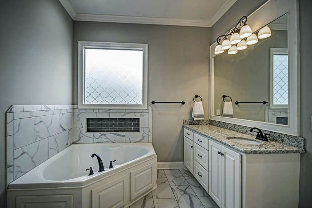 Primary bathroom with a sink vanity and a corner bathtub accentuated with a marble backsplash.
