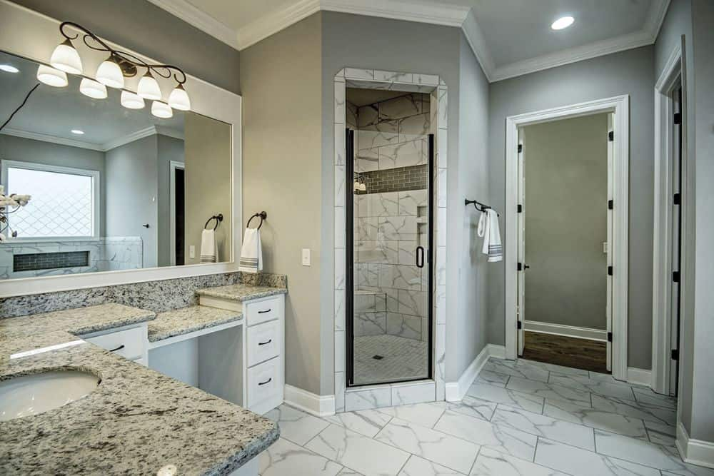 A walk-in shower enclosed in a glass hinged door completes the primary bathroom.