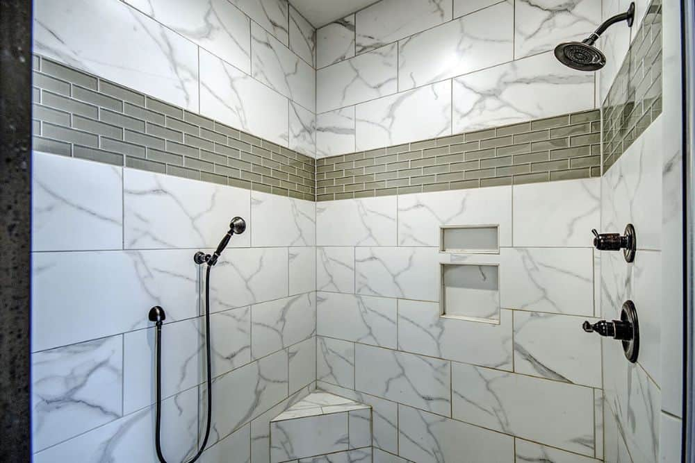 The walk-in shower has marble tiled walls, wrought iron fixtures, inset shelves, and a corner seat.