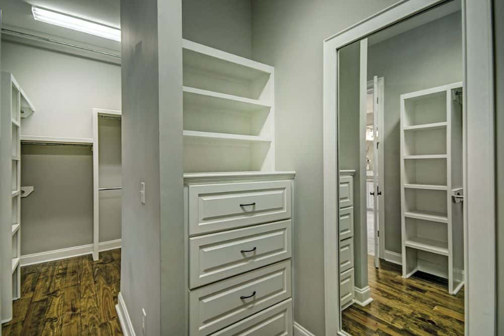 Primary walk-in closet with large mirrors and built-in shelves.