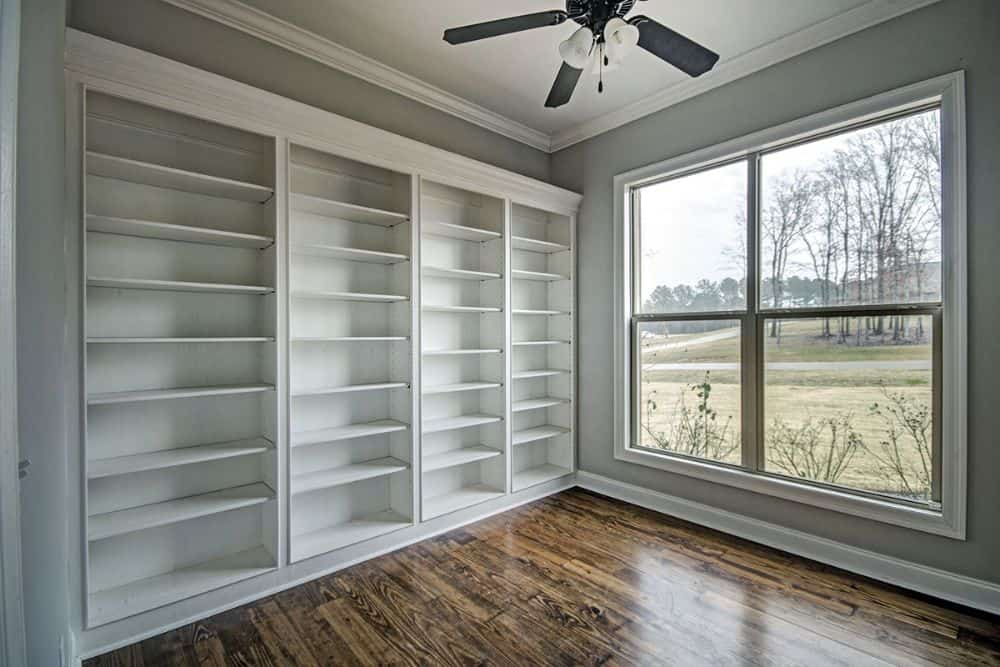 Home office with white built-in shelves and a large window overlooking the serene surrounding.