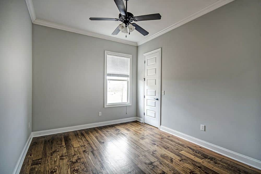 Bedroom with hardwood flooring and gray walls lined with white moldings.