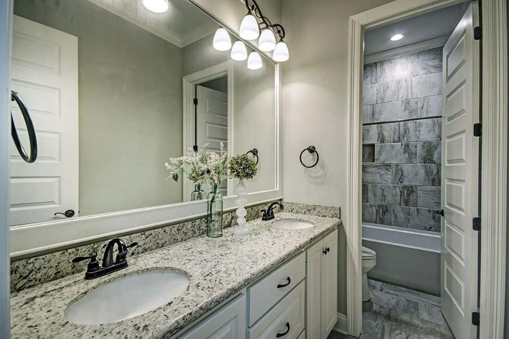 This bathroom is equipped with a double sink vanity, a toilet, and a tub and shower combo.