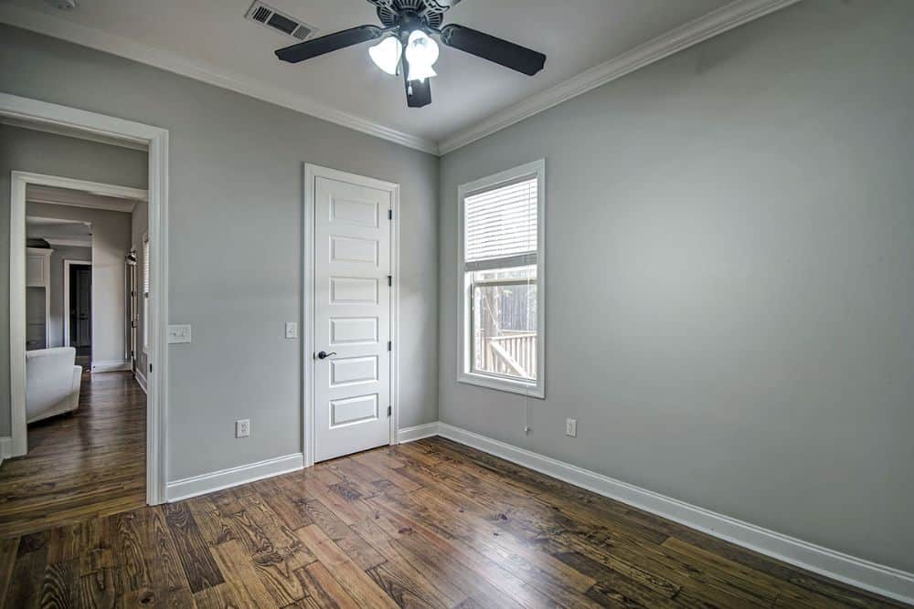 Another bedroom with gray walls, hardwood flooring, and a walk-in closet concealed behind the white door.