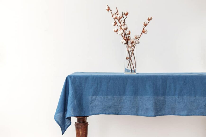 This is a close look at a console table with a blue linen tablecloth on it.