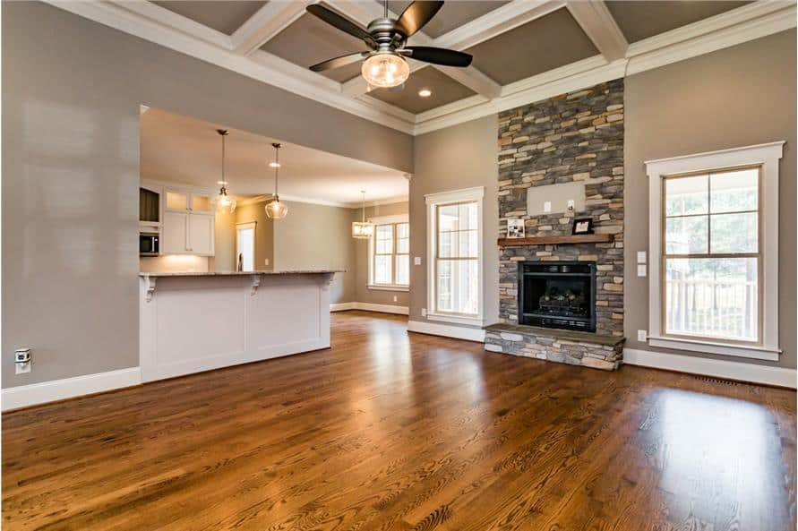 The living room features a stone fireplace and a coffered ceiling mounted with a fan.