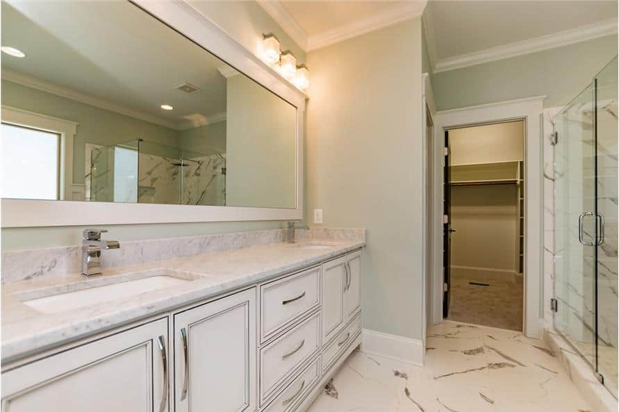 The primary bathroom is equipped with a walk-in shower and closet along with a dual sink vanity.