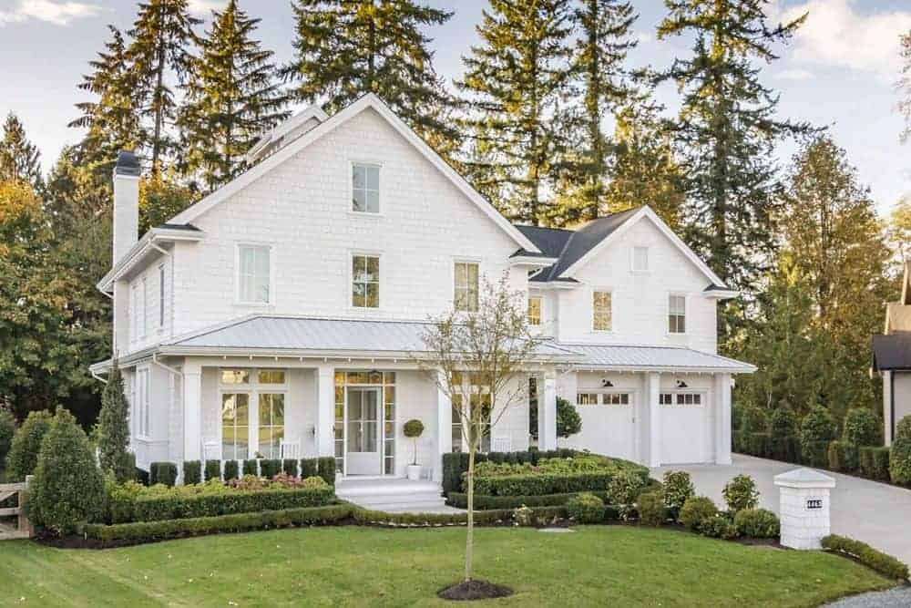 Verdant landscaping featuring manicured shrubs and a well-maintained lawn complements the two-story farmhouse.