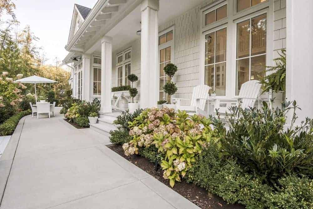 The covered porch has decorative columns, white rocking chairs, and fresh potted plants.