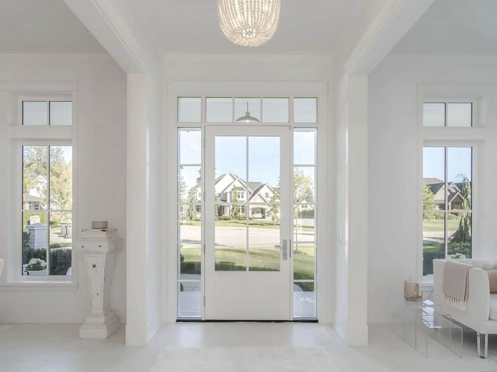 Foyer with a beaded chandelier and a glass entry door surrounded by transom and sidelights.