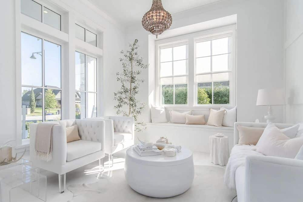 The parlor room offers white tufted seats, a round coffee table, and a window seat filled with white and blush pillows.