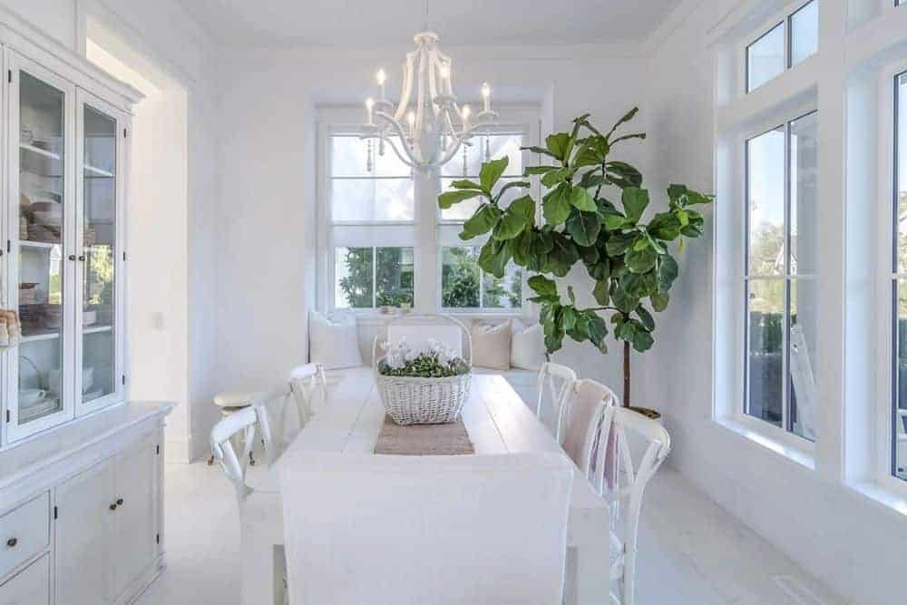 Another window seat can be seen in the dining room. There's also a rectangular dining set, white china cabinet, a candle chandelier, and a large potted plant.
