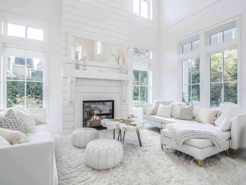Living room with white sectional sofas, matching ottomans, a stump coffee table, and a glass-enclosed fireplace.
