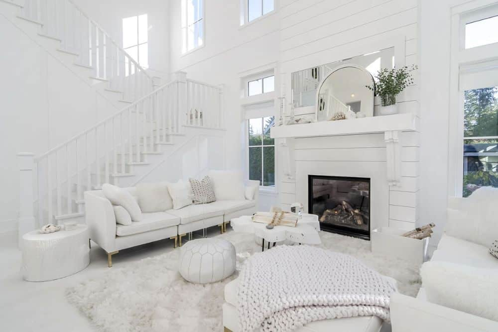 A white staircase next to the living room leads to the upstairs bedrooms.