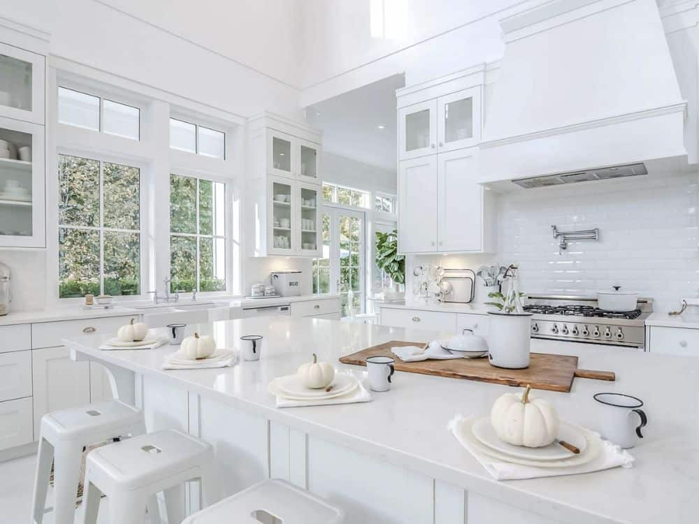 White framed windows and doors flood the kitchen with natural light.