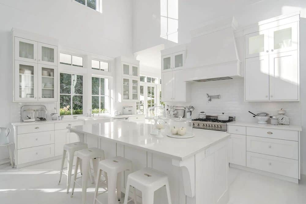 Kitchen with white and glass-front cabinets, stainless steel cooking range, subway tile backsplash, and a breakfast bar lined with white bar stools.