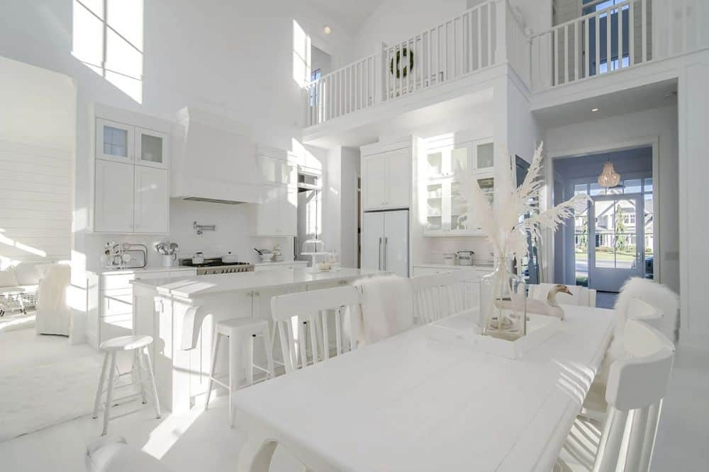 The dining area is furnished with a rectangular dining table and matching white chairs.