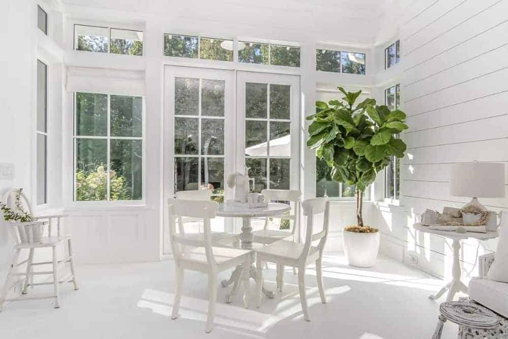 Breakfast nook with a round dining set, a fresh potted plant, and a french door that grants access to the backyard.