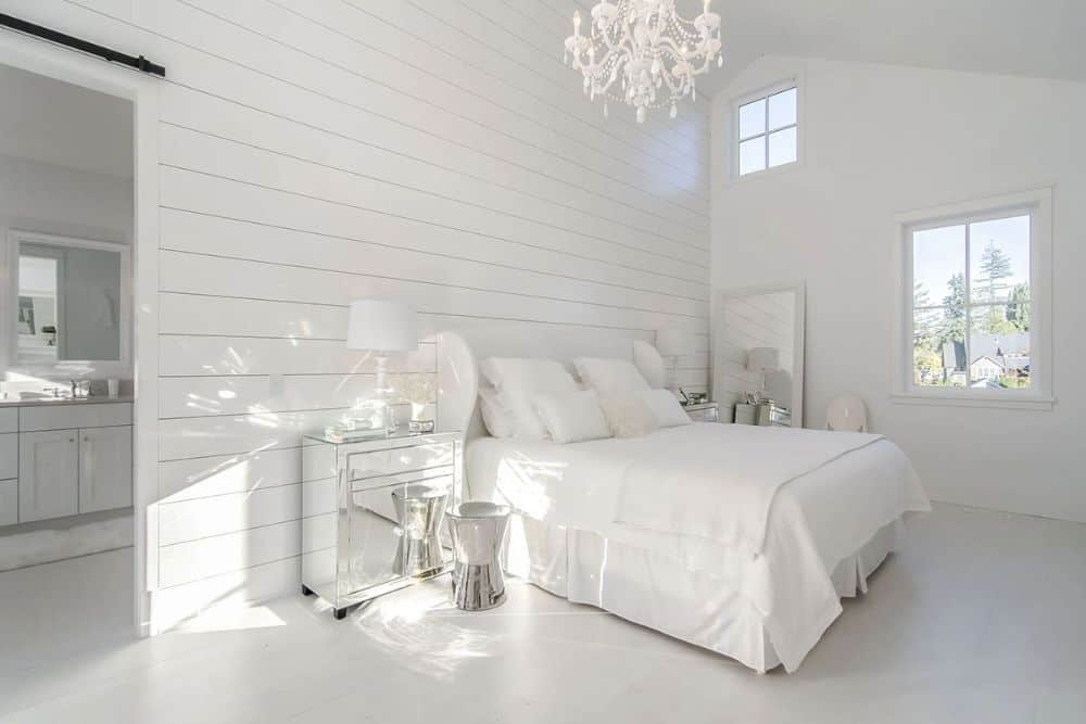 Primary bedroom with a white shiplap accent wall, white furnishings, and a vaulted ceiling mounted with a fancy beaded chandelier.