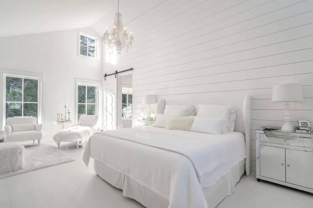 The primary bedroom includes a spacious sitting area filled with white seats and a plush rug.