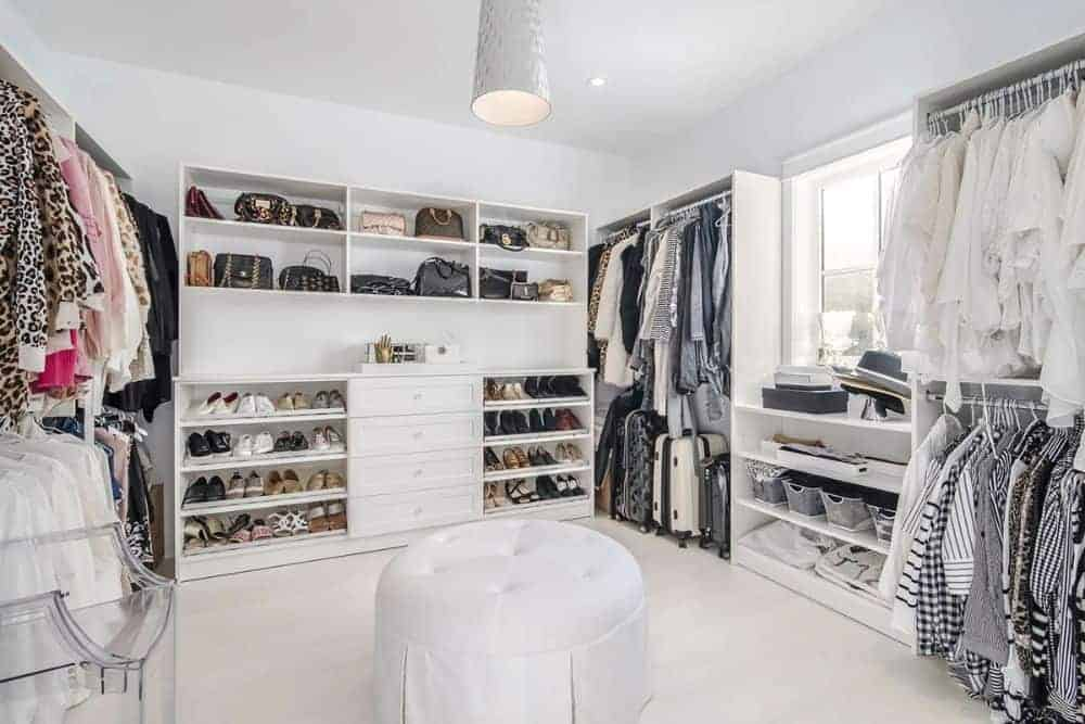 Primary walk-in closet with white built-ins and a round tufted ottoman over the light hardwood flooring.