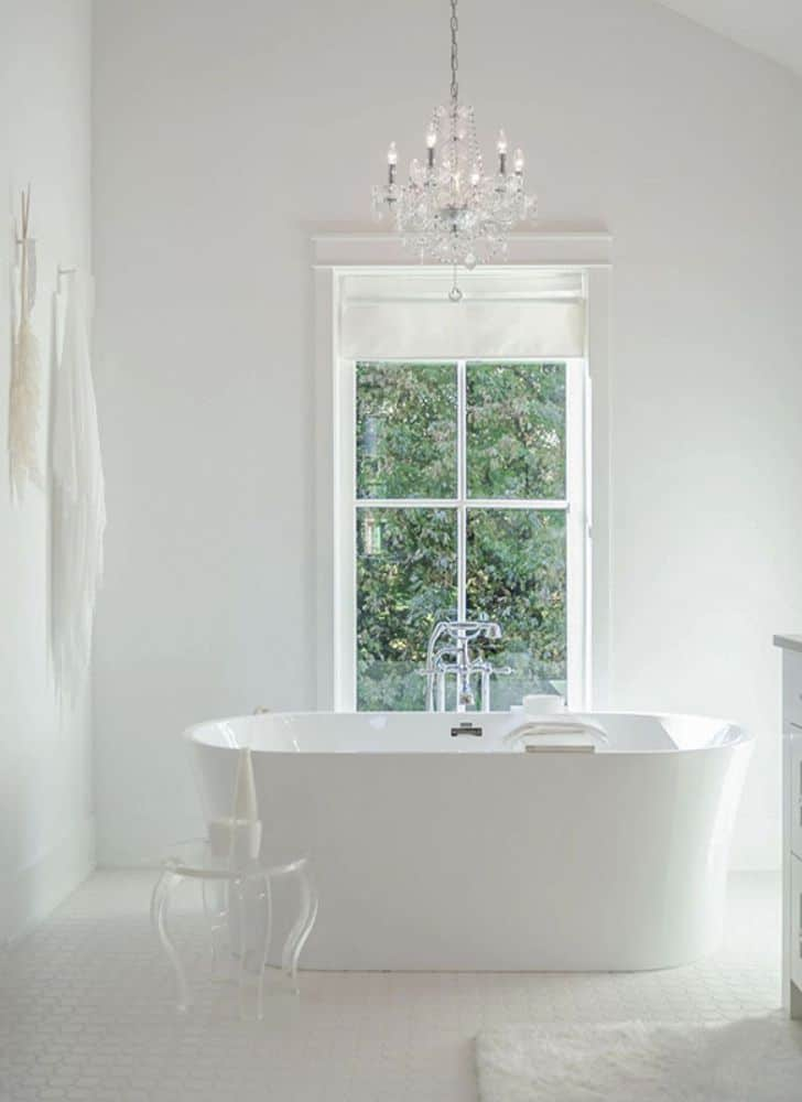 The primary bathroom features a freestanding tub complemented with a ghost side table and a crystal chandelier.