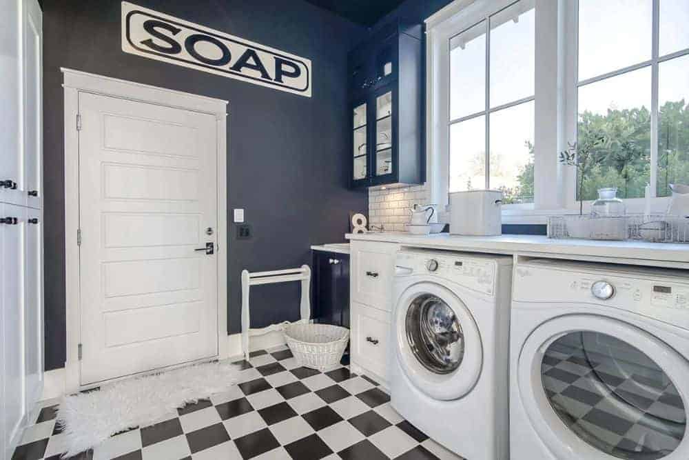 Laundry room with white front-load appliances, deep blue accent wall, white-framed windows, and a checkered flooring topped with a faux fur rug.