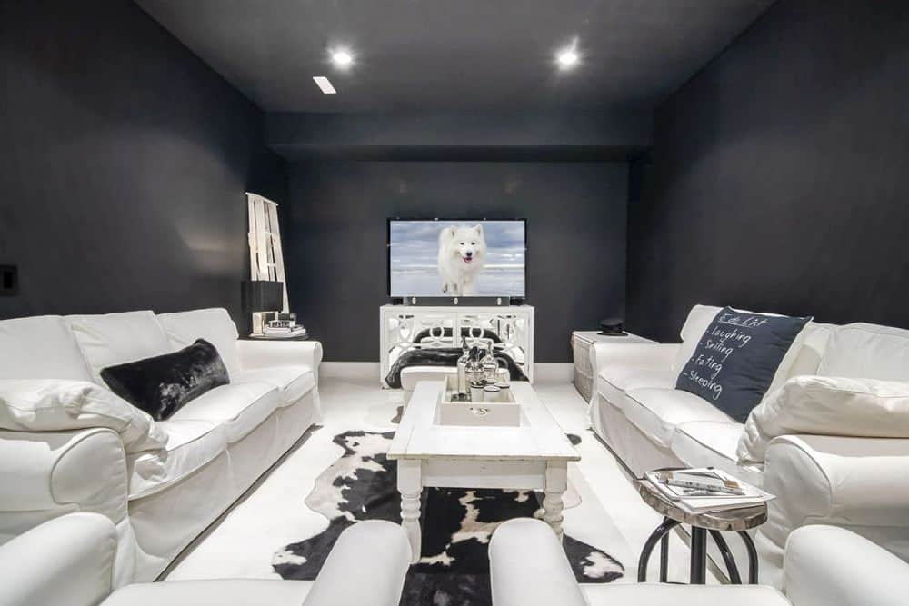 The media room features black walls which set a stunning contrast to the white sectionals, armchairs, and coffee table.