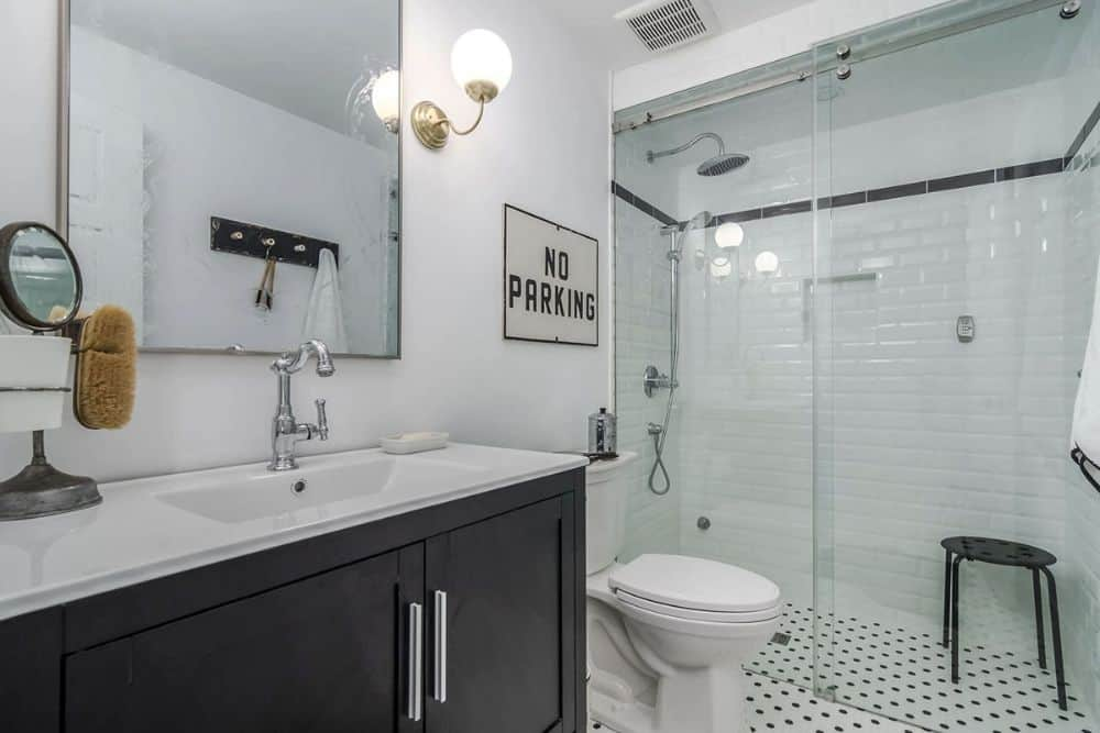 This bathroom offers a sink vanity, a toilet, and a walk-in shower with chrome fixtures and a round stool.