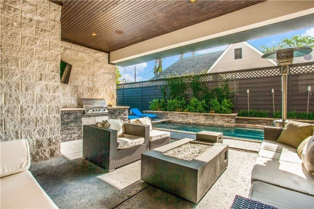 The outdoor living is filled with wicker cushioned seats, a fire pit, and a summer kitchen.