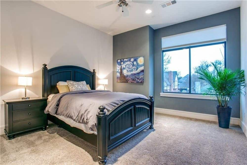 Primary bedroom with dark wood furnishings, carpet flooring, and gray walls adorned with a painting.