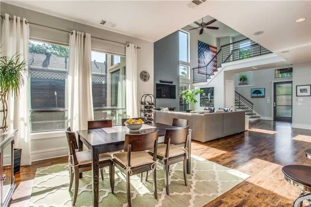The breakfast nook offers a rectangular dining table and matching cushioned chairs sitting on a patterned area rug.