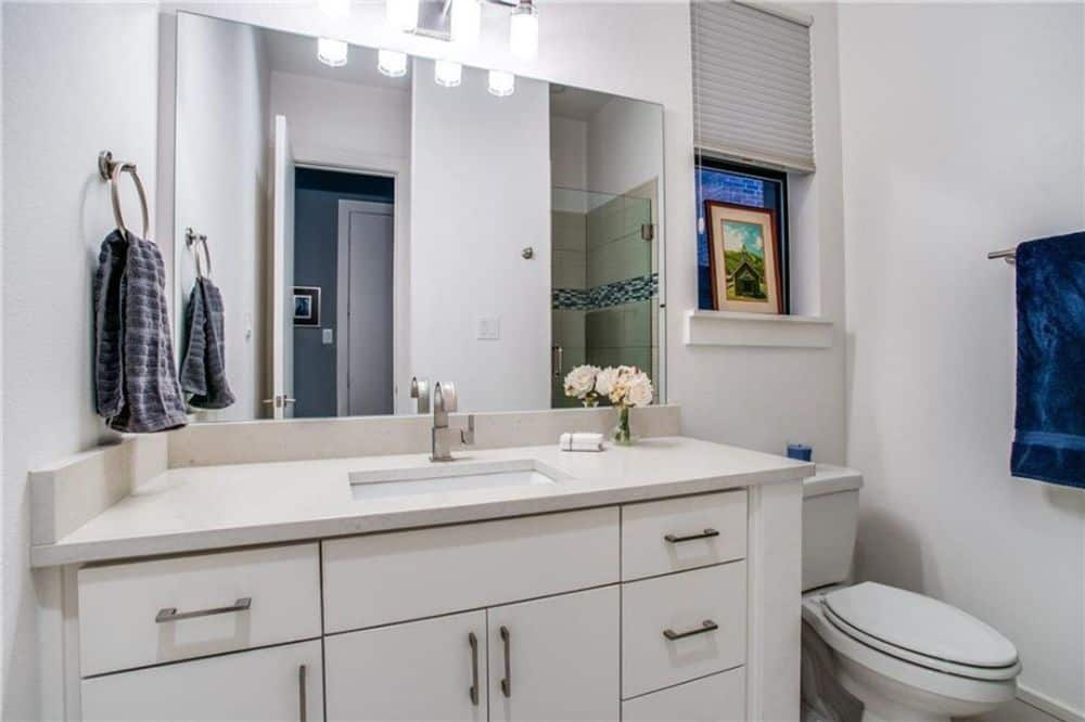 This bathroom is equipped with a single sink vanity, a toilet, and a walk-in shower reflected in the frameless mirror.