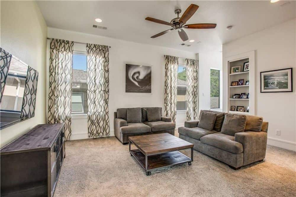 Game room with brown velvet sofas, a wooden coffee table, a TV, and picture windows dressed in patterned draperies.