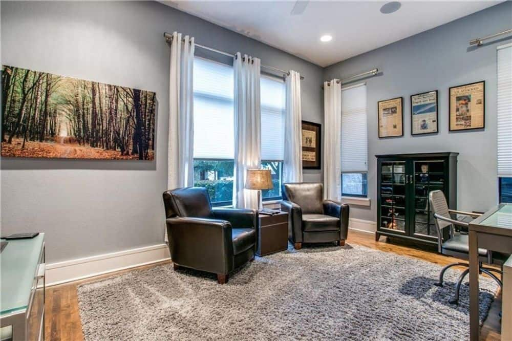 Study with leather armchairs, a shaggy area rug, and a wooden desk paired with a swivel chair.