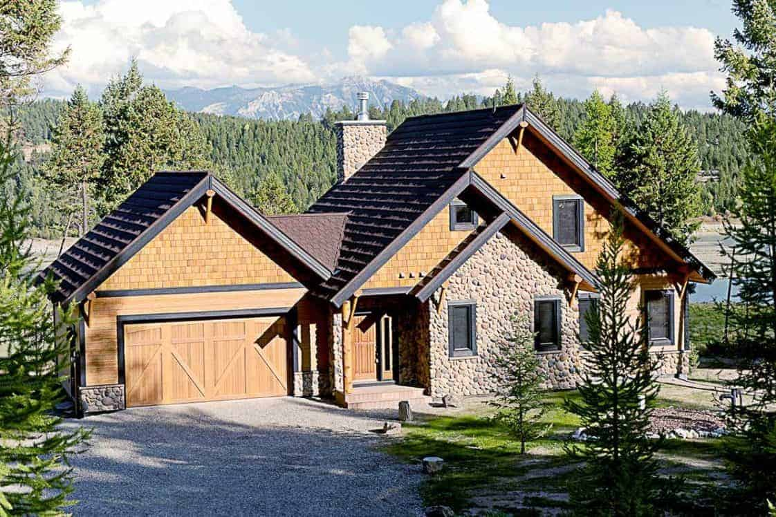 This is a front view of the house with agraveled driveway and walkway complemnted by the large grass lawn dotted with various pine trees that go well with the earthy tones of the house exterior.