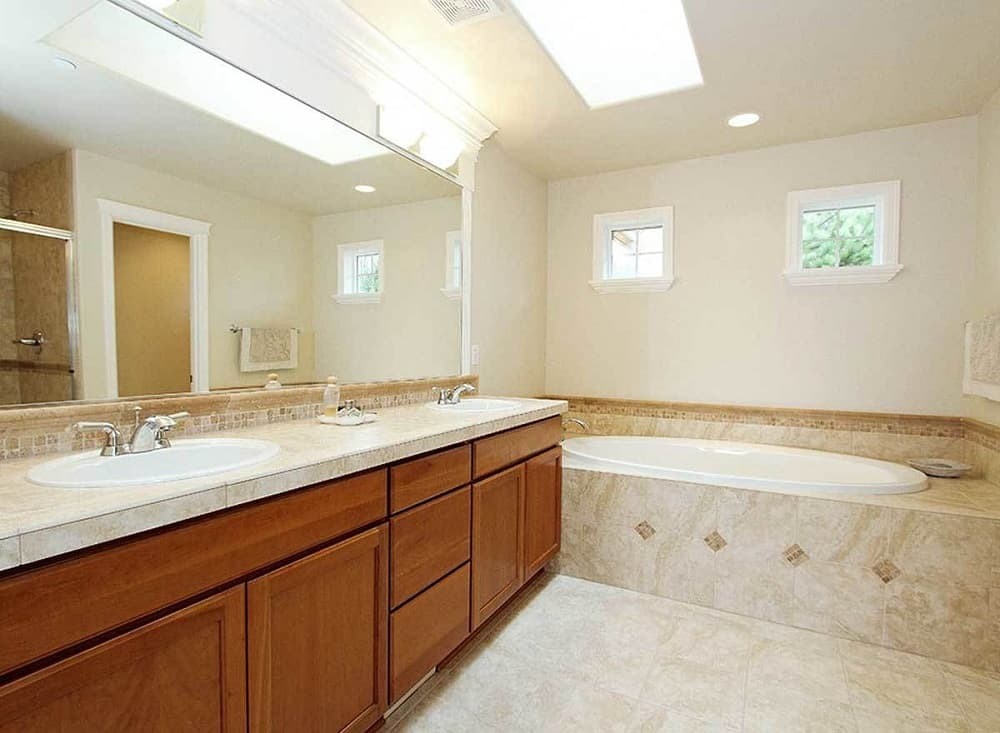 This is the simple primary bathroom that has a large two-sink vanity with brown wooden drawers topped with a large wall-mounted mirror beside the bathtub on the far side. These are brightened by the skylight above.