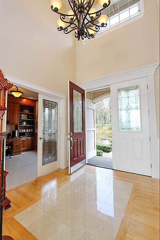 This is a close look at the foyer that has a set of double doors with glass panels to brighten the hardwood flooring and tall beige walls topped with a large chandelier.