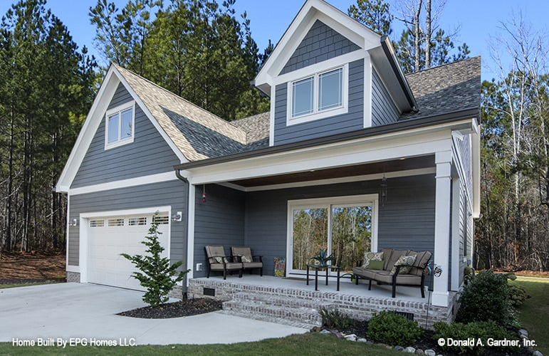 Rear exterior view with a double garage and a covered porch topped with a large gable dormer.