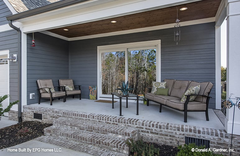 A closer look at the rear covered porch with cushioned sectional, matching sofas, and a dark wood coffee table.