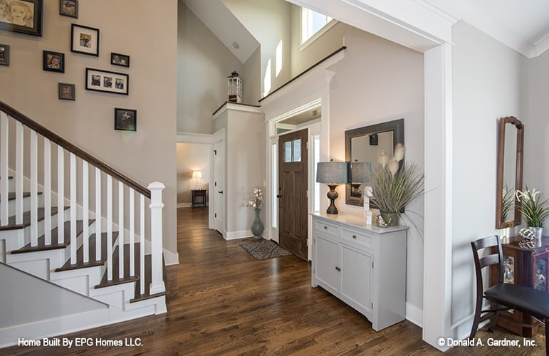 The foyer has a vaulted ceiling, a wooden entry door, and a console table adorned with a framed mirror.