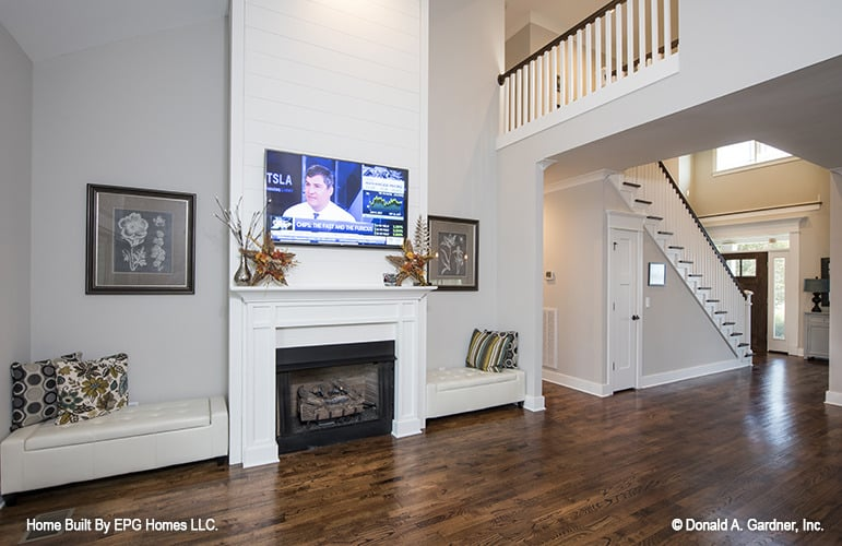 Great room with a wall-mounted TV and a fireplace flanked by tufted seats.