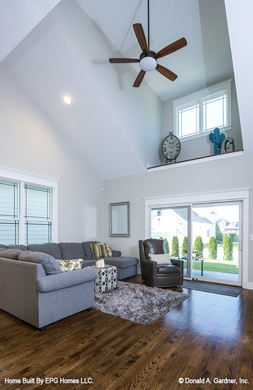 The great room includes an L-shaped sectional, leather armchair, and sliding doors that lead to the rear patio.