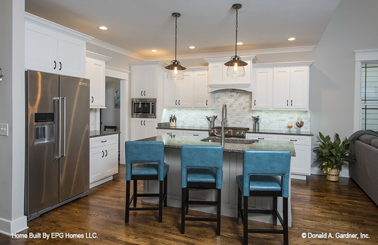 The kitchen is equipped with stainless steel appliances, white cabinetry, and a breakfast island paired with blue leather stools.