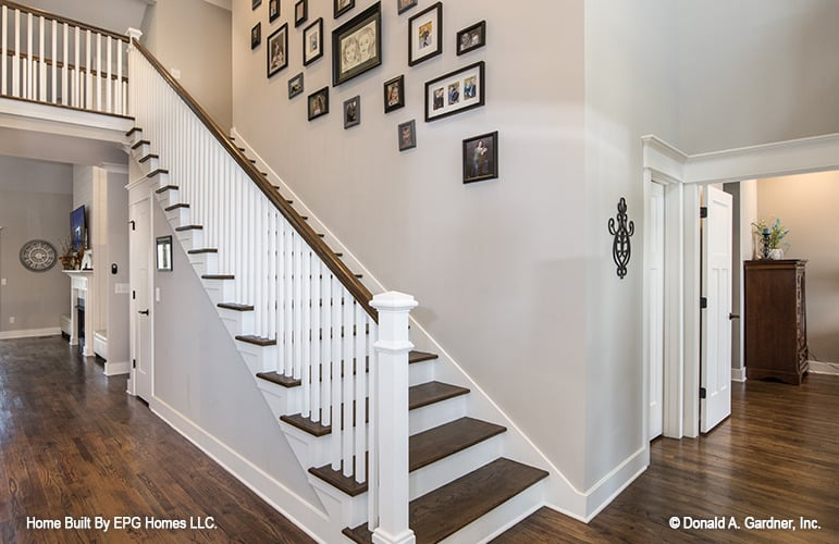 A wooden staircase fixed against a gallery wall leads to the upstairs bedrooms.
