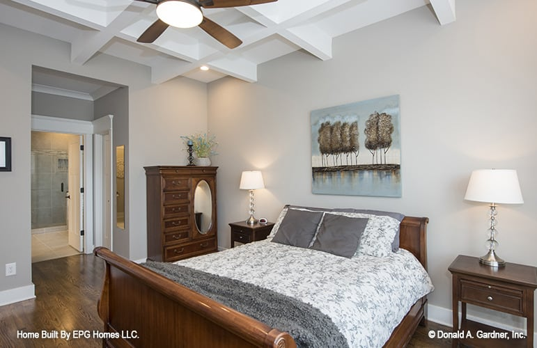 The primary bedroom features a coffered ceiling, dark wood furnishings, and gray walls decorated with a landscape painting.