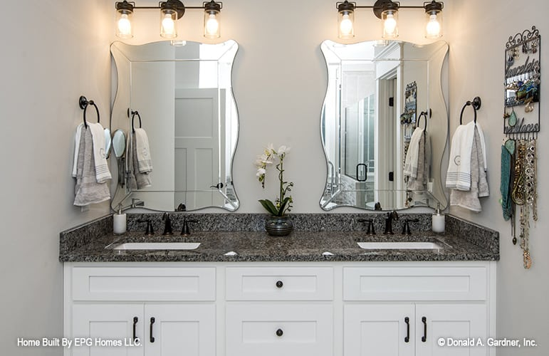 A granite top vanity with double sinks and frameless mirrors completes the primary bathroom.
