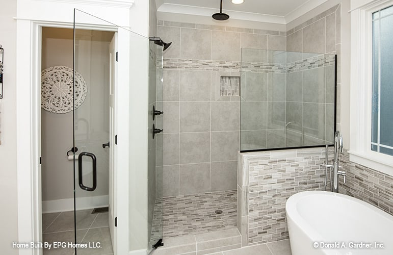Primary bathroom with a walk-in shower, a water closet, and a freestanding tub.