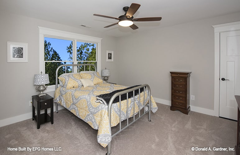 This bedroom offers a ceiling fan and a metal bed over carpet flooring.